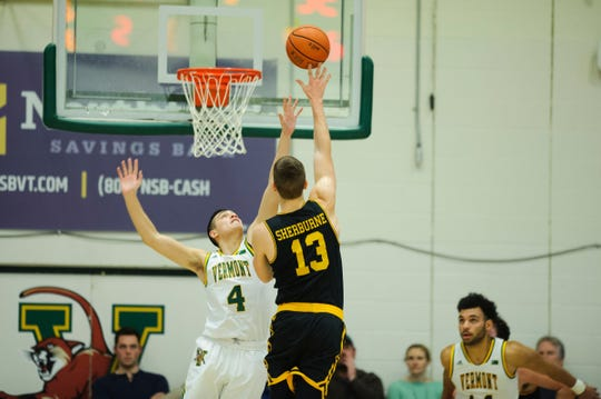 UMBC's Joe Sherburne (13) shoots the ball over Vermont guard Robin Duncan (4) during the men's basketball game between the UMBC Retrievers and the Vermont Catamounts at Patrick Gym on Wednesday night January 23, 2019 in Burlington, Vermont. (