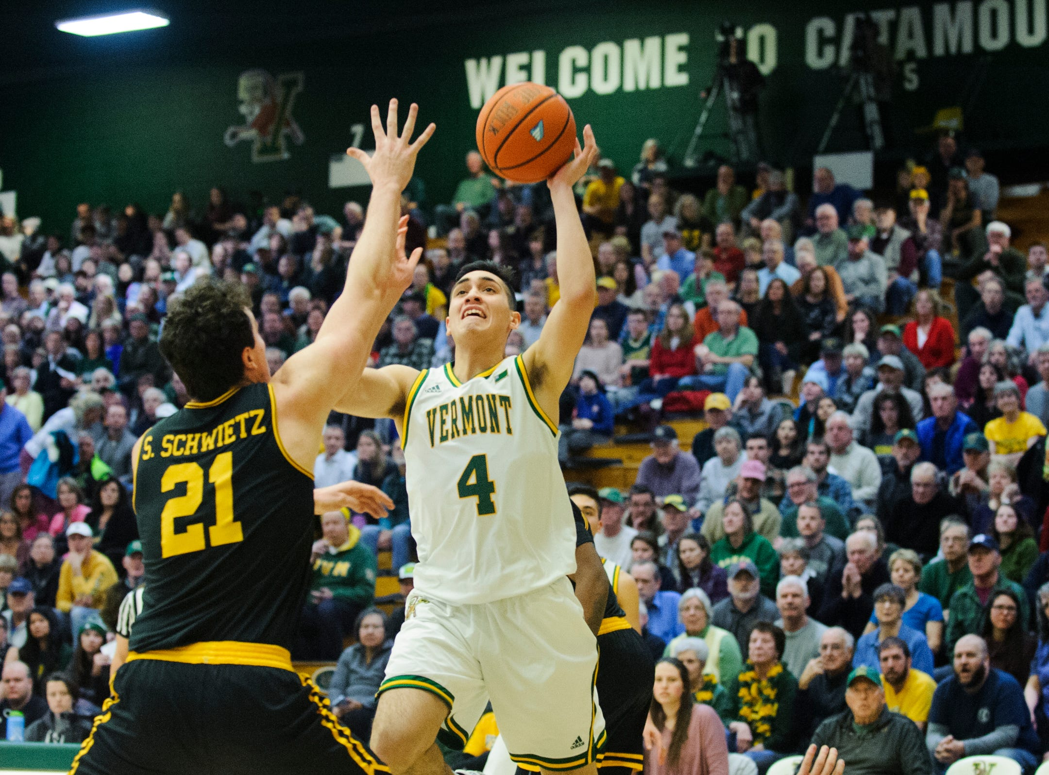 Vermont guard Robin Duncan (4) shoots the ball over UMBC's Sam Schwietz (21) during the men's basketball game between the UMBC Retrievers and the Vermont Catamounts at Patrick Gym on Wednesday night January 23, 2019 in Burlington, Vermont.