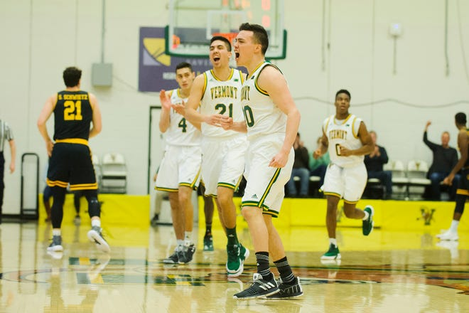Vermont guard Ernie Duncan (20) celebrates a 3-pointer during the men's basketball game between the UMBC Retrievers and the Vermont Catamounts at Patrick Gym on Wednesday night. Brothers Everett and Robin Duncan are in the background.