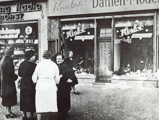 A group of people stand outside a Jewish-owned shop in an unnamed German town in November 1938, after the Kristallnacht, when Nazis thugs burned and plundered hundreds of Jewish homes, shops and synagogues across the country. (AP Photos)
