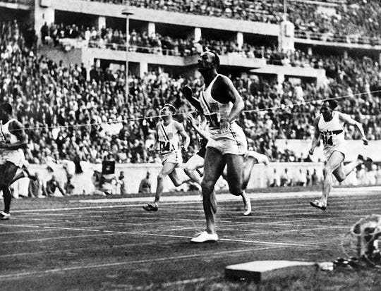 """U.S. champion """"Jesse"""" (James Cleveland) Owens crosses the finish line of the 100m event, that he won, on Aug. 5, 1936, during the Olympic Games in Berlin."""