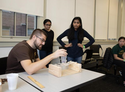 """At the New Jersey Science Olympiad at NJIT, middle and high school students engaged in """"Mystery Architecture,"""" which provided a bag of materials with instructions for designing and building a testable device — in this case, a bridge assembled from straws and Scotch tape. The UPS-sponsored event gave participants 30 minutes to construct their bridges, putting their physics knowledge to work. Each bridge was then placed atop a wood structure with a small plastic cup resting in the middle. Activity administrators dropped pennies in the cup one at a time until the bridge collapsed, counting the number of pennies and measuring the distance from where the bridge fell to the wood structure. This team from Robert R. Lazar Middle School fared well — 25 pennies and 6-1/4 inches."""