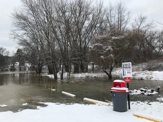 Water is standing in the parking lot of the Second Street boat ramp due to the rising Muskingum River.