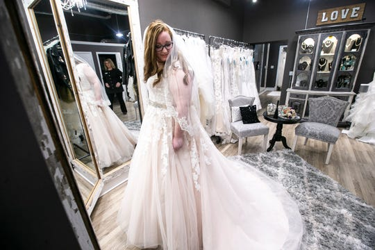 Kaitlin McNary tries on a wedding dress on Thursday, Jan. 24, 2019, at Hitched Bridal and Formal Wear in Bloomfield, Iowa. McNary is a former Hitched employee who is getting married in September.