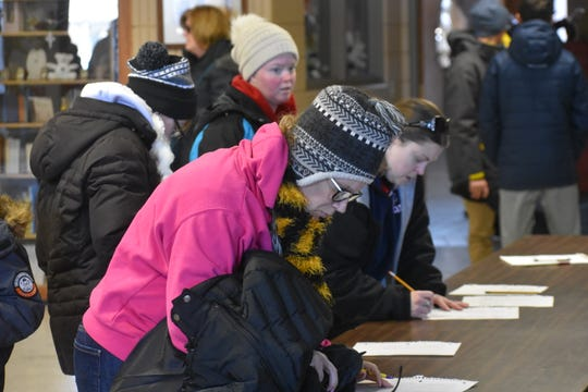 Dozens of Marshalltown-area residents in the St. Henry Catholic Church cafeteria sign up to help locate missing boy Corey Brown on Wednesday, Jan. 23, 2019.