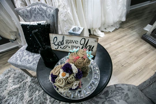 """A sign reads, """"God gave me you,"""" on a table in the fitting area on Thursday, Jan. 24, 2019, at Hitched Bridal and Formal Wear in Bloomfield, Iowa."""