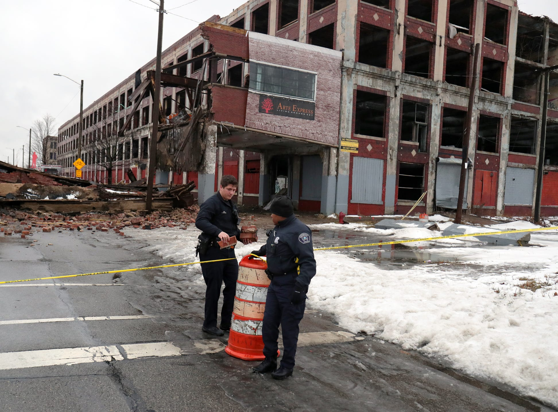 Detroit police officers Jon Morden and Kimberley Wright secure the area around the collapsed Packard Plant bridge on Grand Boulevard Wednesday, January 23 , 2019 in Detroit, Mich.
