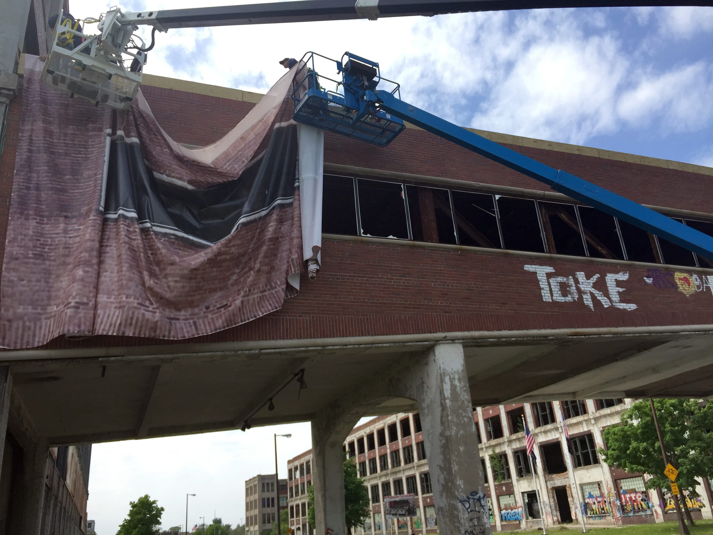 Work crews at the Packard Plant on Thursday draped a graphic covering over both sides of the iconic pedestrian bridge across East Grand Boulevard. The heavy mesh covering depicts the bridge as it looked during its early 20th Century heyday.