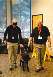 On March 19, 2018 Phil Bertolini wore a blindfold and let Flaim, a 2-year-old male black Labrador Retriever, lead him as part of Leader Dogs for the Blind's executive training. Mike Toger of Leader Dogs for the Blind is on the right.