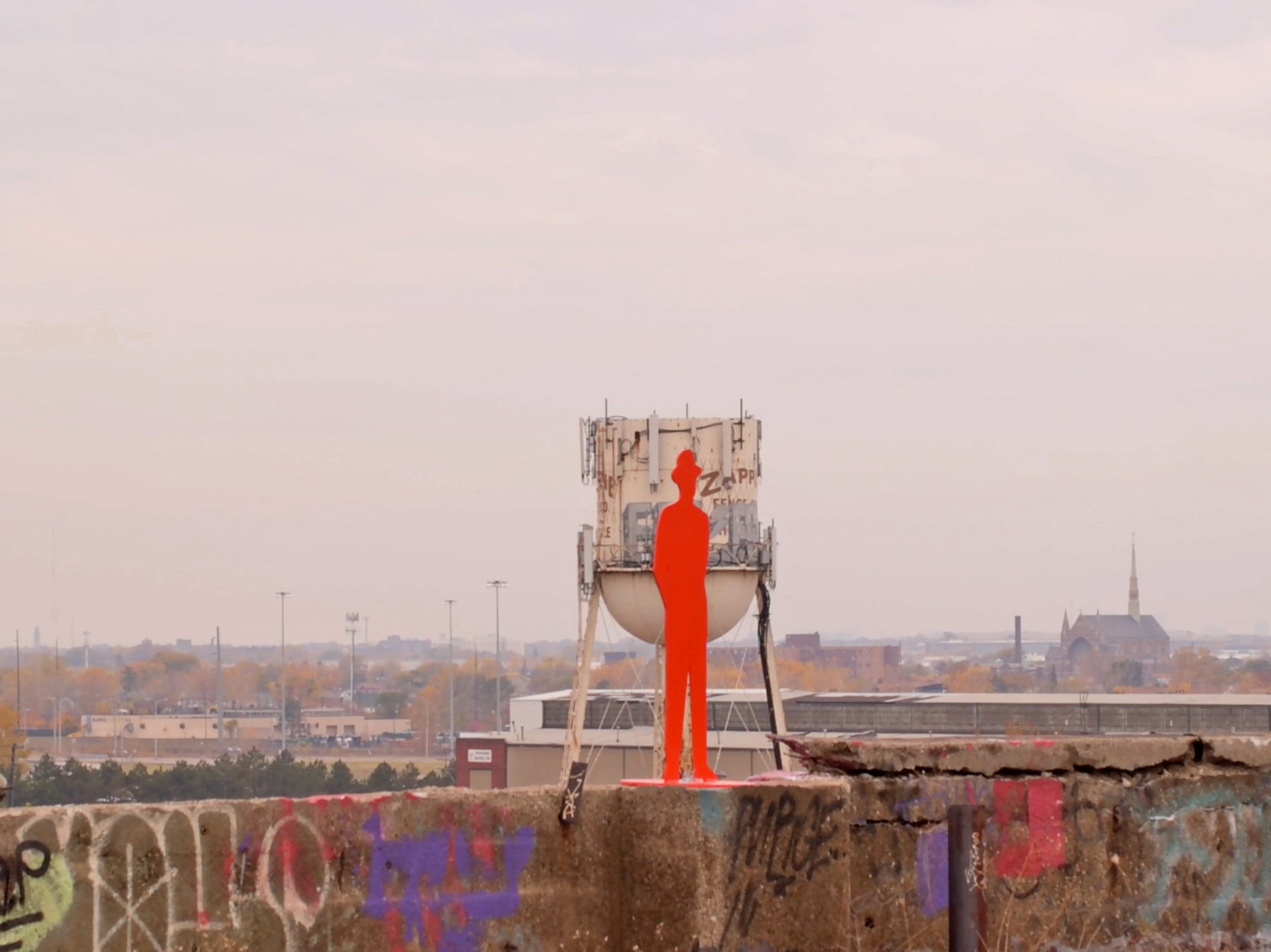 Part of John Sauve's Man in the City urban exhibition, the orange sculpture of a man adorns the Packard Plant roof in Detroit, Mich. on Saturday, October 24, 2015.