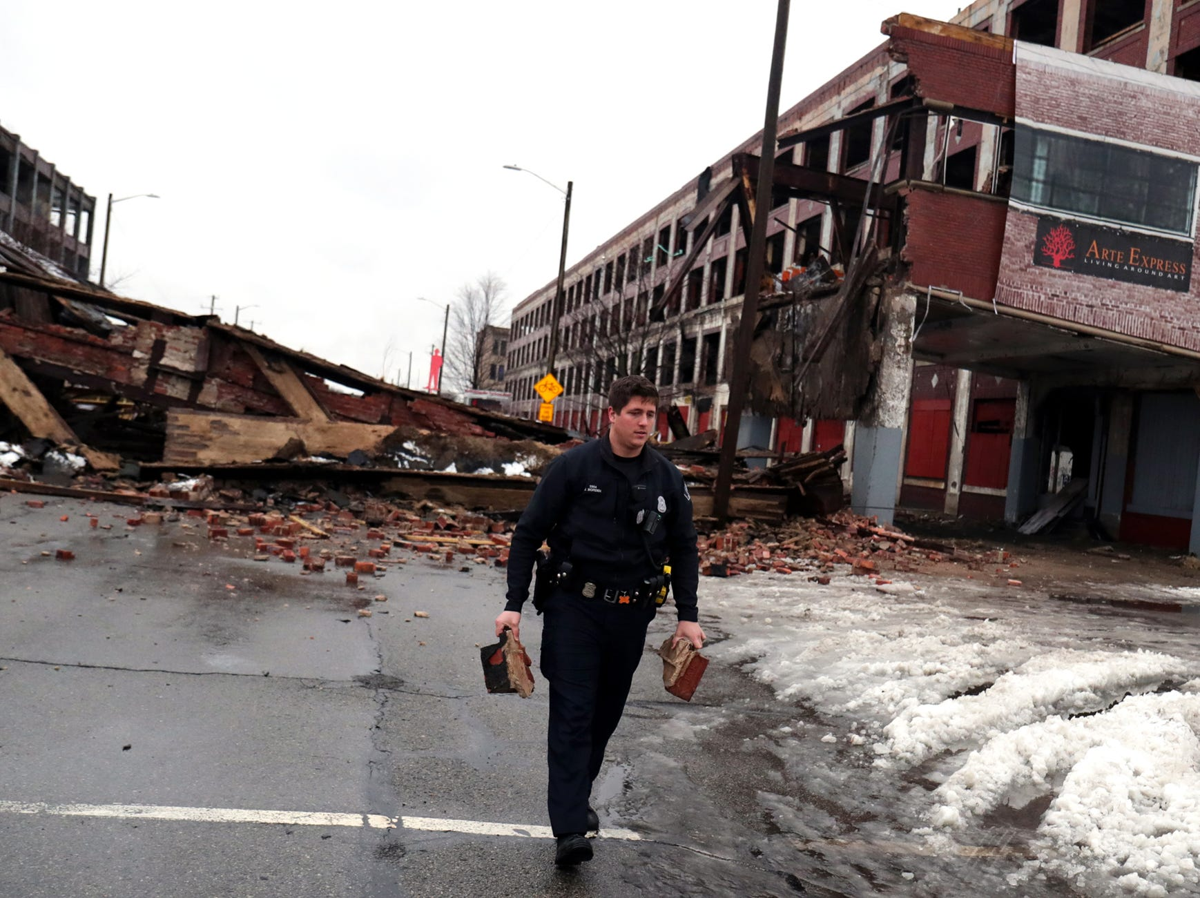 Detroit police officer Jon Morden uses bricks from the collapsed Packard Plant bridge to hold up a barrier blocking off Grand Boulevard Wednesday, January 23 , 2019 in Detroit, Mich.