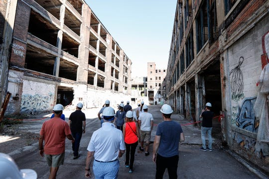Pure Detroit's guided tour gather between the final inspection building, left, and administration building, right, at the Packard Plant, Sunday, September 24, 2017 in Detroit.