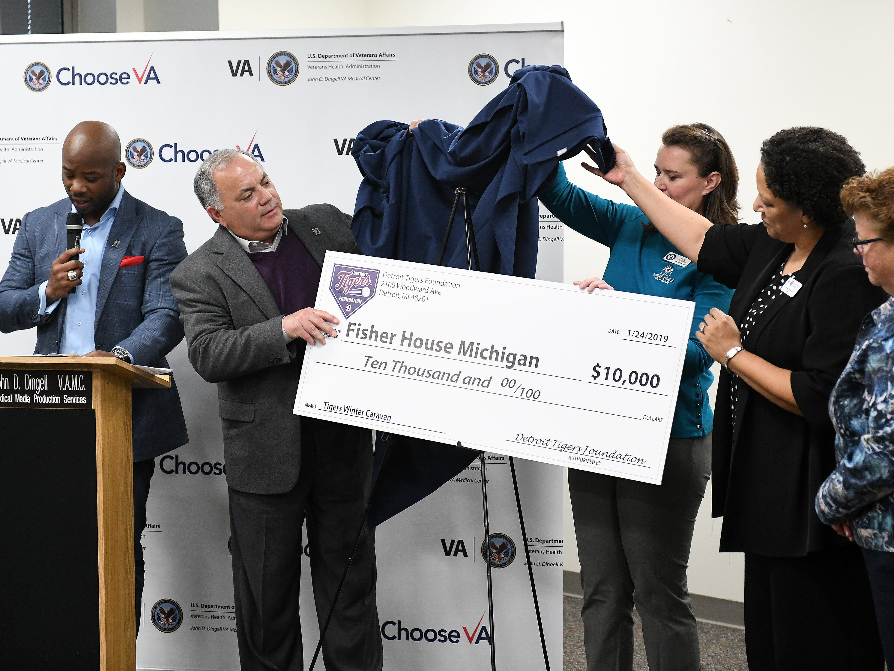 Tigers executive vice president of baseball operations and general manager Al Avila unveils a check towards the Fisher House which will be built near the VA Medical Center during a stop on the 2019 Detroit Tigers Winter Caravan at the John D. Dingell VA Medical Center in Detroit on Jan. 24, 2019.
