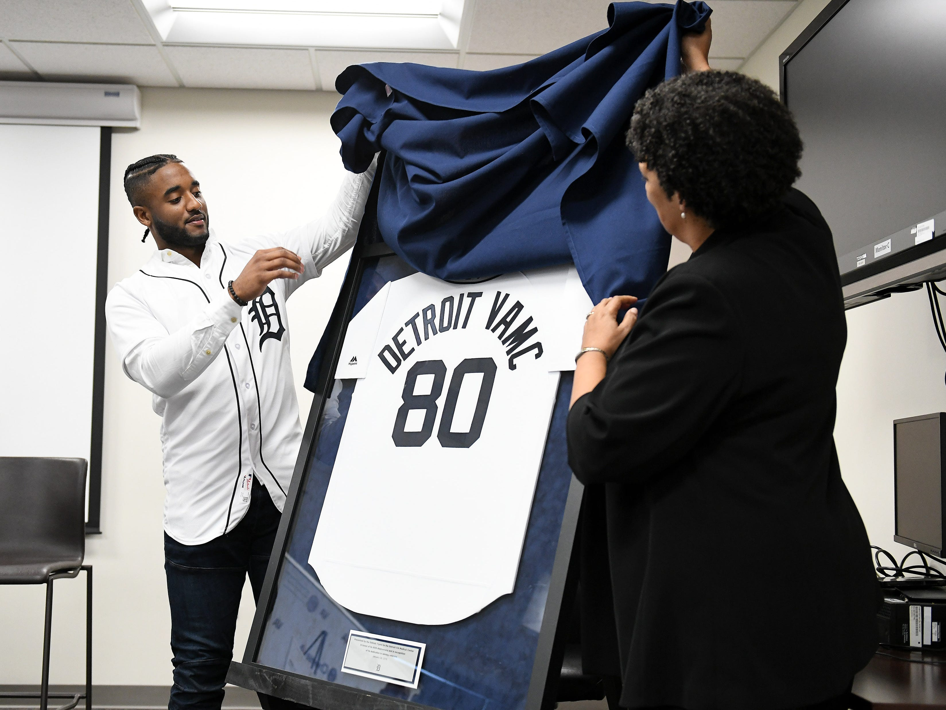 Tigers' Niko Goodrum, left, and John D. Dingell VA Medical Center director Pamela J. Reeves, MD, unveil a special jersey celebrating 80 years of service by the Detroit VA Medical Center during a stop on the 2019 Detroit Tigers Winter Caravan at the John D. Dingell VA Medical Center in Detroit on Jan. 24, 2019.