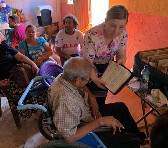 Detroit News columnist Maureen Feighan gives out reading glasses as part of a medical mission trip to El Salvador in January.