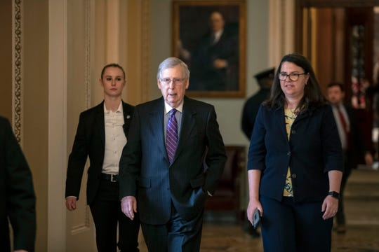 Senate Majority Leader Mitch McConnell, R-Ky., with Secretary for the Majority Laura Dove, right, walks from the chamber at the Capitol in Washington, Wednesday, Jan. 23, 2019.