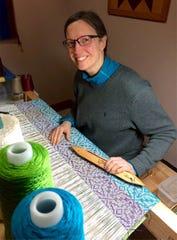 Sondra Hoffman works at a floor loom.