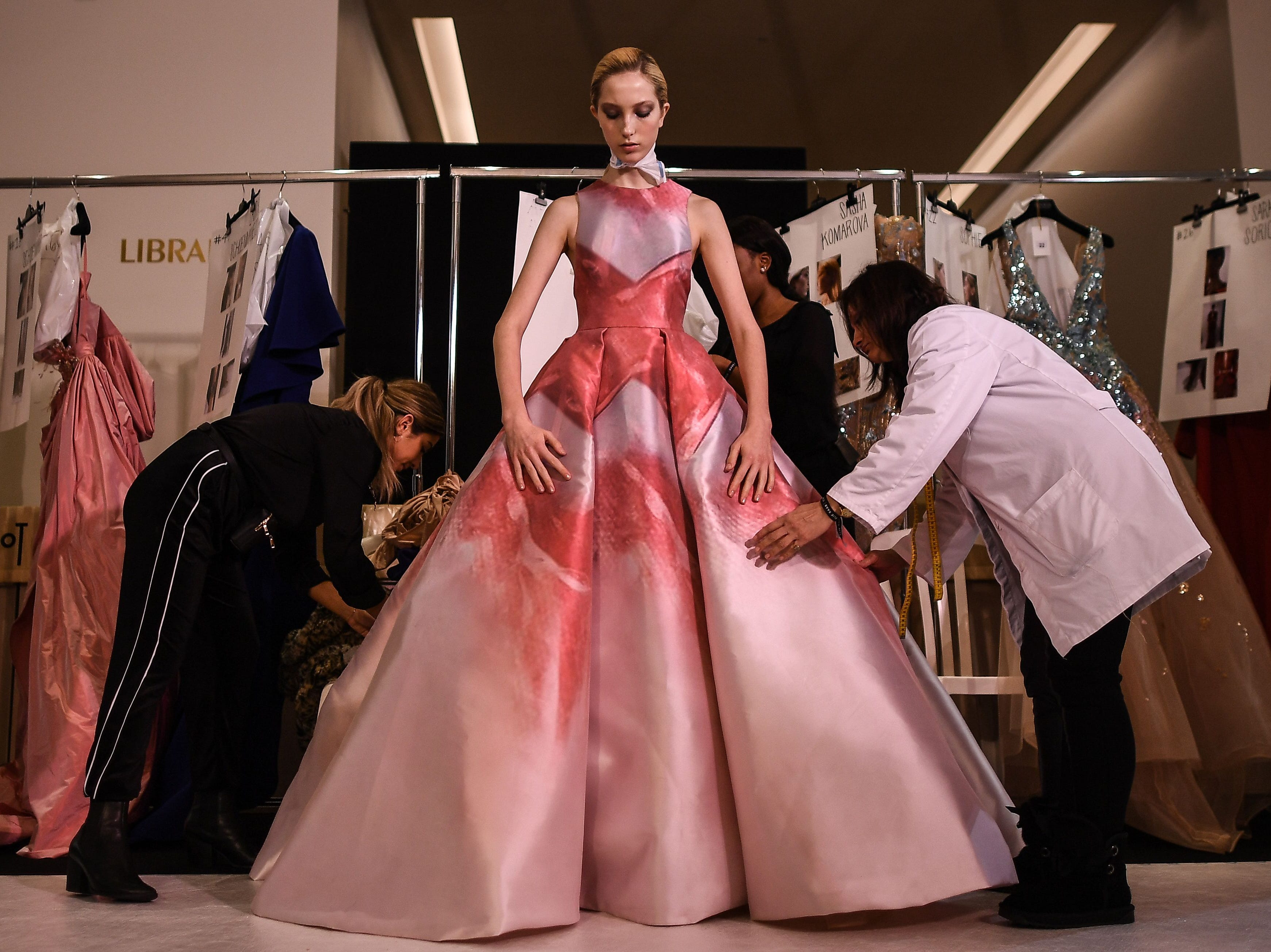 Assistants dress a model prior to the Elie Saab 2019 Spring-Summer Haute Couture collection fashion show in Paris, on January 23, 2019.