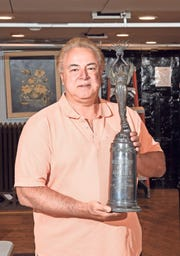Alan Cavrell with his  1943 Swanson roller skating trophy at the DuMochelles Art Galleries in Detroit