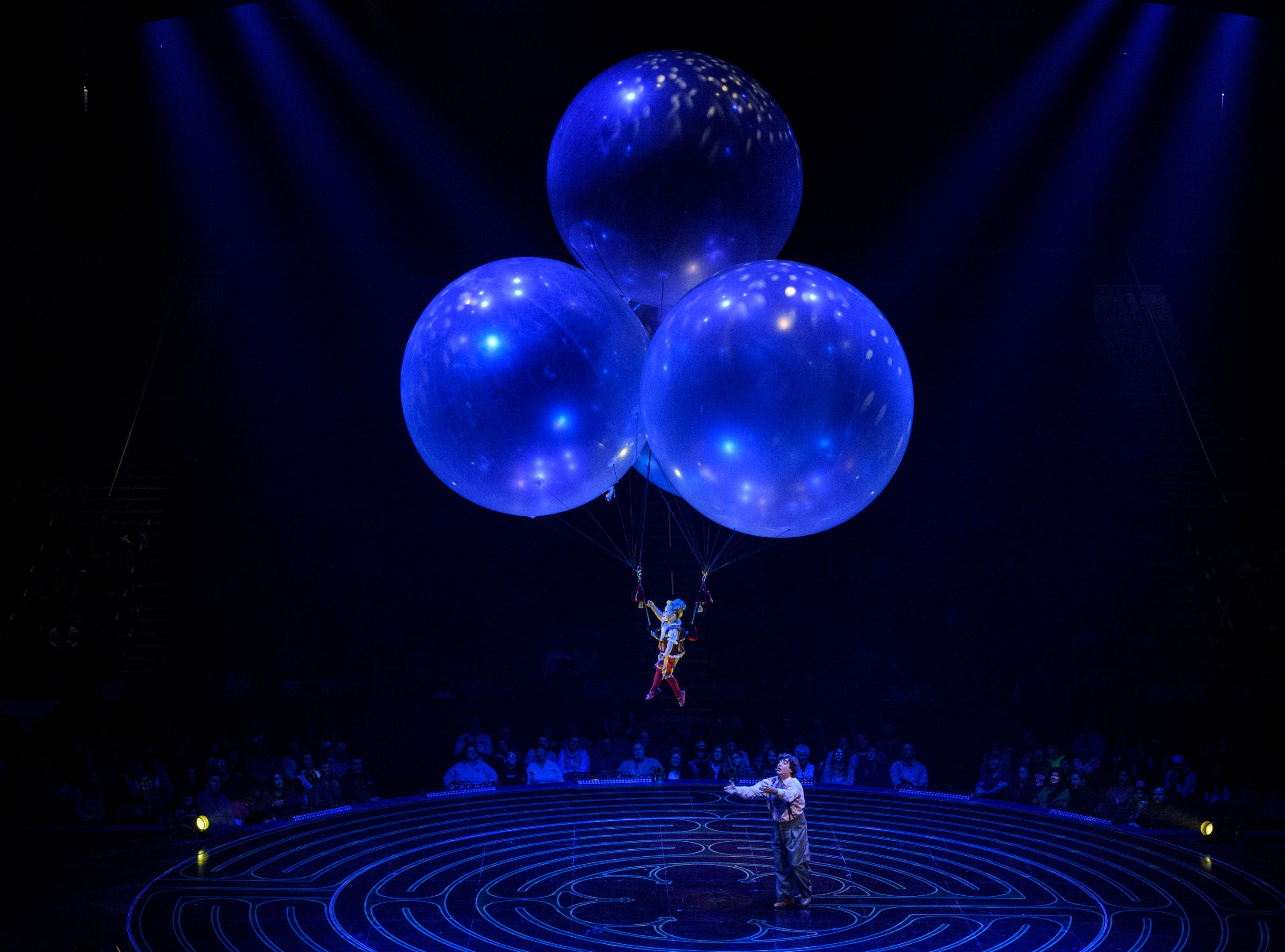 Valentyna Pahlevanyan, top, leaves Mauro the Dreamer Clown, played by Lolo Fernández, bottom, on stage to float around the crowd from three large balloons during Cirque du Soleil's Corteo show at Ford Center in Evansville, Ind., Wednesday night, Jan. 23, 2019.