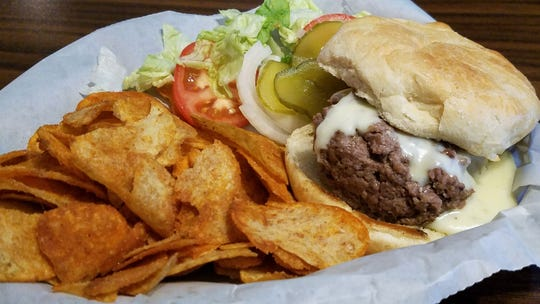 A steam burger from Mojo's BoneYard is a juicy baseball-sized patty drenched in melted white cheese on a toasted bun.