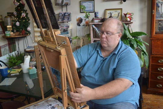 Rob Brown works on a caricature inside Main Street Café in downtown Clyde.