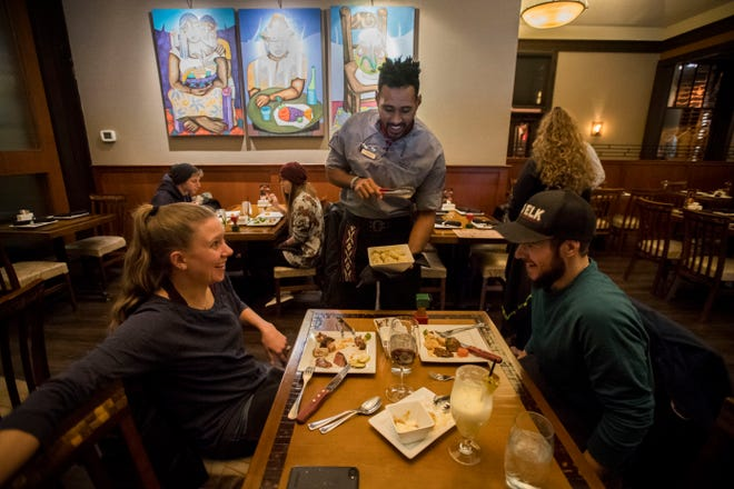 Gaœcho Leividy Souza serves a dish to Sydney Wells and Jamison Wicks, who came in for dinner to celebrating of their shared birthdays, on Wednesday, Jan. 23, 2019, at Rodizio Grill in Fort Collins, Colo.