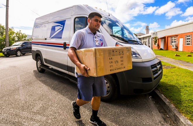 Vince Castro, United States Postal Service city carrier assistant, delivers a parcel to a customer in downtown Hagåtña on Thursday, Jan. 24, 2019.