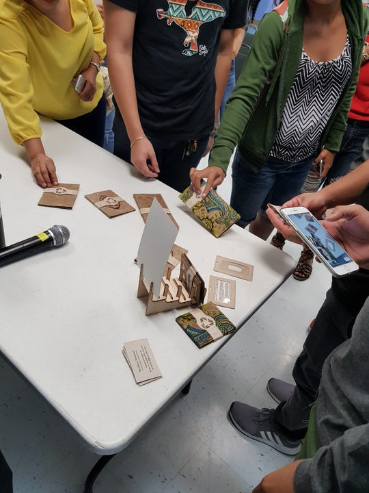 GCC students and other community members check out Matthew Simpson's display of wallets from Green Banana Paper.