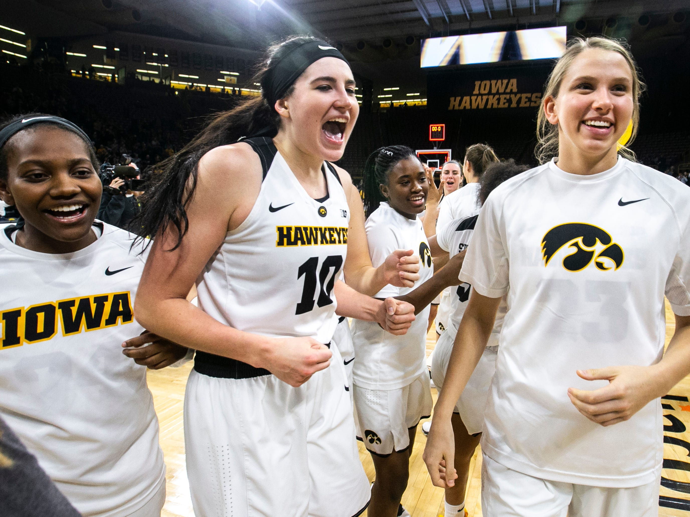 Iowa forward Megan Gustafson (10) celebrates with teammates Logan Cook, right, and Zion Sanders during a NCAA Big Ten Conference women's basketball game on Wednesday, Jan. 23, 2019, at Carver-Hawkeye Arena in Iowa City, Iowa.