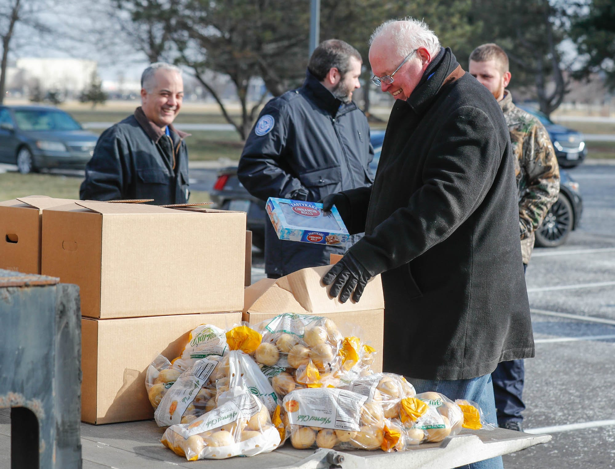 Community volunteer and Old Bethel UMC member, Ron Phillips, center front, hands out Gleaners Food Bank boxes to TSA  employees affected by the government shutdown at the Transportation Security Administration offices, 8303 W Southern Ave., Indianapolis, on Thursday, Jan. 24, 2019.