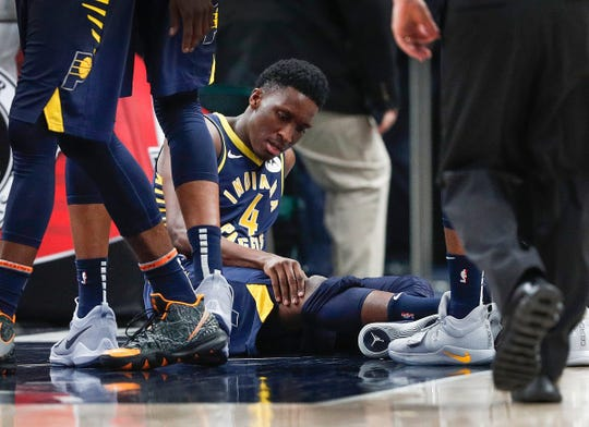 Indiana Pacers guard Victor Oladipo holds his right knee after tumbling to the court while defending against the Toronto Raptors. Jan. 23, 2019