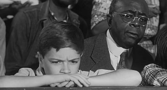 """Jem"" Finch (Phillip Alford) and  Reverend Sykes (William ""Bill"" Walker) in the courtroom scene of To Kill a Mockingbird."