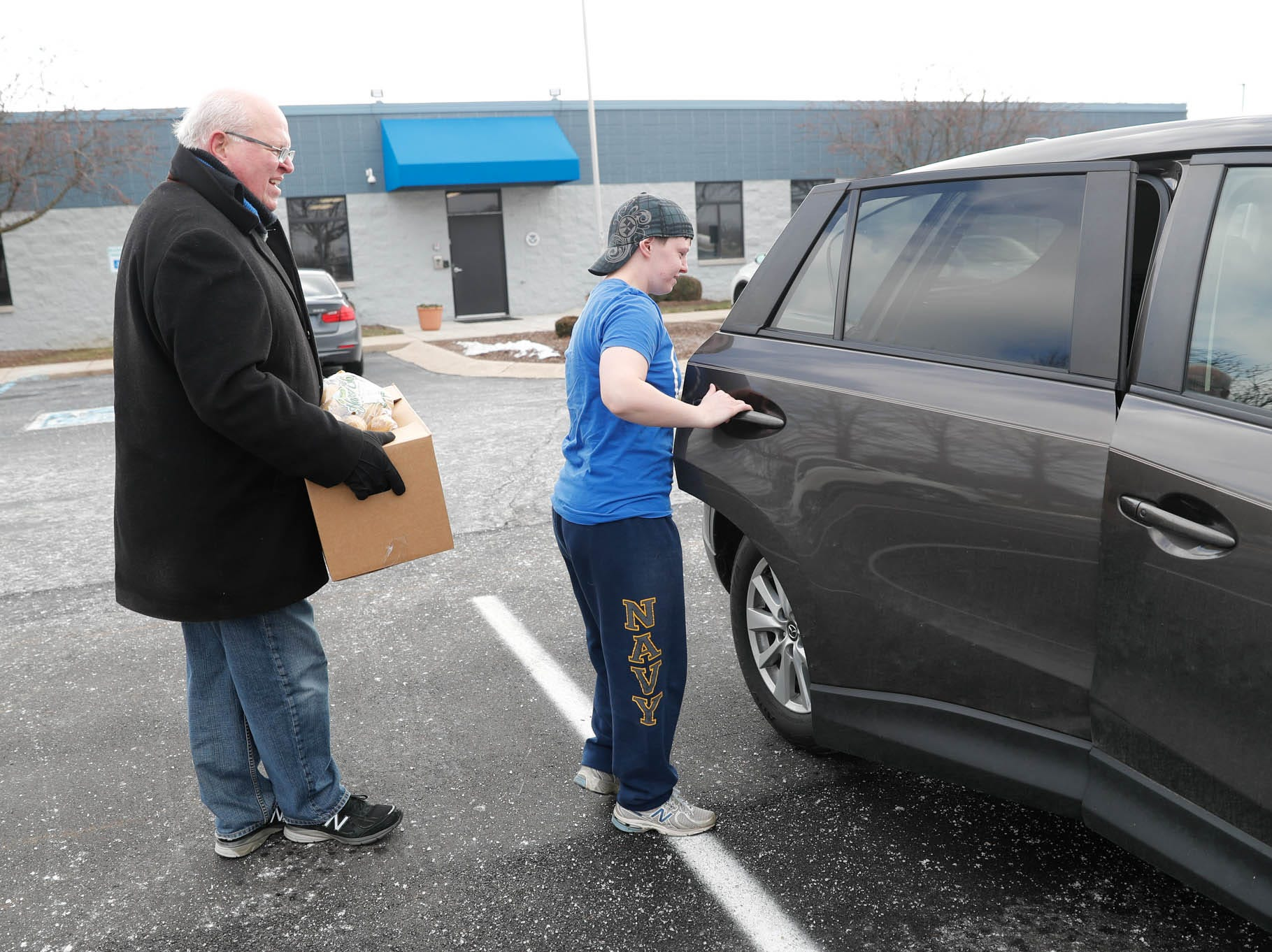 Community volunteer Ron Phillips, from Old Bethel UMC, helps Transportation Security Officer Eileen Jarp, right, to  load a Gleaners Food Bank box for TSA  employees affected by the government shutdown at the Transportation Security Administration offices, 8303 W Southern Ave., Indianapolis, on Thursday, Jan. 24, 2019.