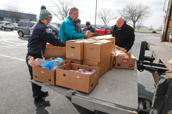 Transportation Security Officer Brandon Cassiday, left, picks up a Gleaners Food Bank box from Old Bethel UMC volunteers, for TSA  employees affected by the government shutdown at the Transportation Security Administration offices, 8303 W Southern Ave., Indianapolis, on Thursday, Jan. 24, 2019.