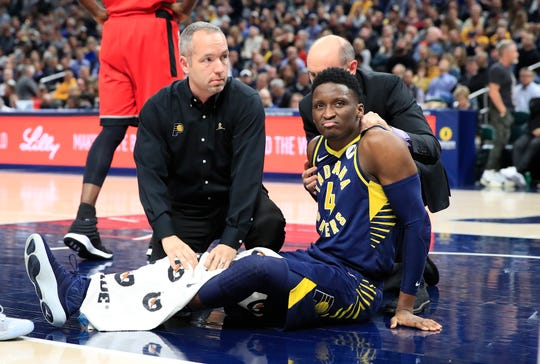 Victor Oladipo #4 of the Indiana Pacers is attended to by medical staff after being injured in the second quarter of the game against the Toronto Raptors  at Bankers Life Fieldhouse on January 23, 2019 in Indianapolis.