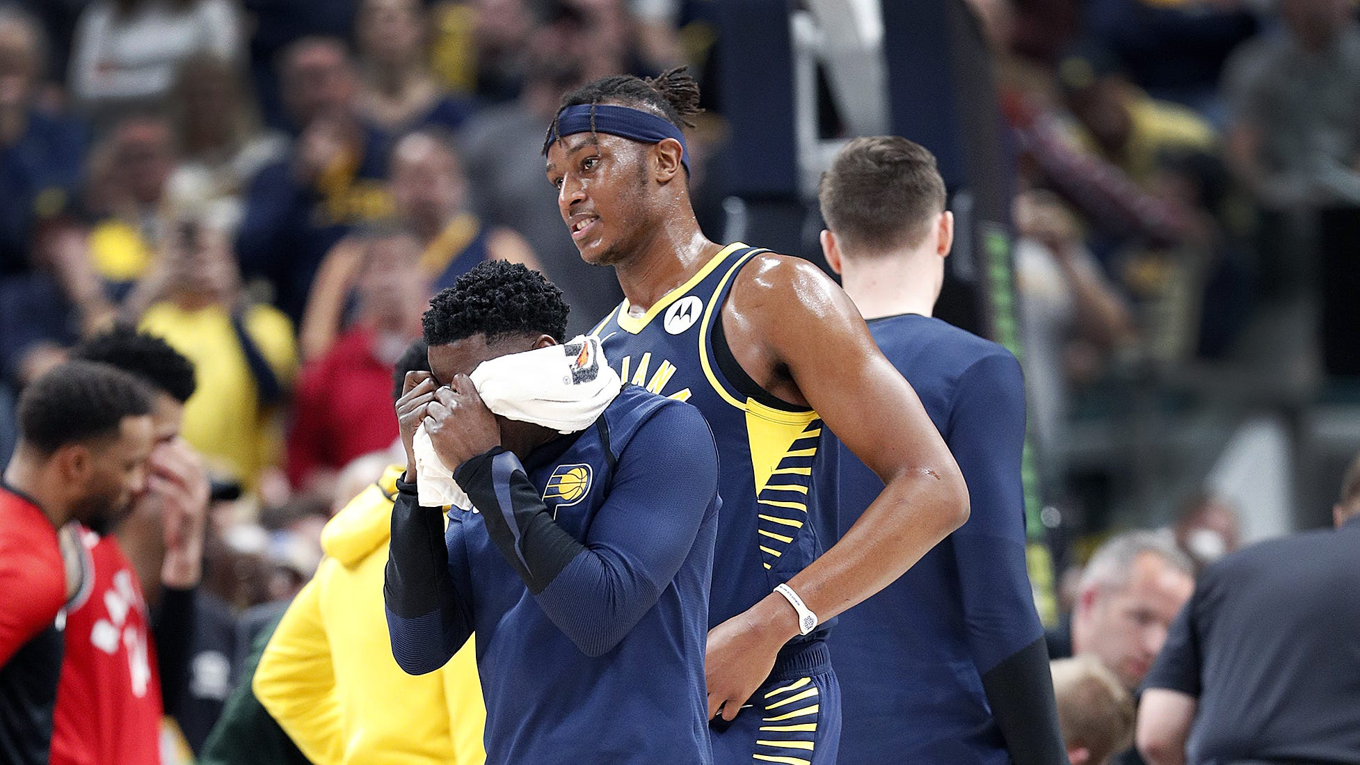 Indiana Pacers guard Darren Collison (2) and Myles Turner (33) can't watch as their teammate Victor Oladipo after he went down with a knee injury  in the first half of their game at Bankers Life Fieldhouse Saturday, Jan. 23, 2019.