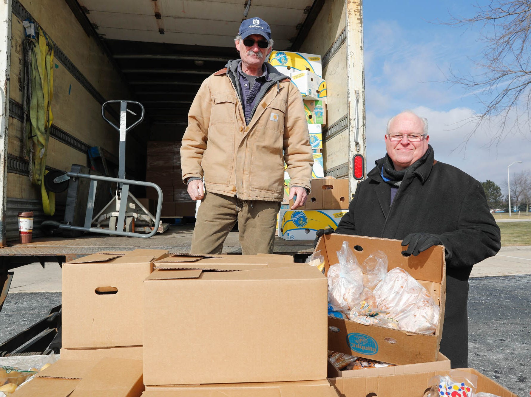 Community volunteers Ron Phillips, right, and Gerald Schneidt, left, with Old Bethel UMC, hand out Gleaners Food Bank boxes to TSA  employees affected by the government shutdown at the Transportation Security Administration offices, 8303 W Southern Ave., Indianapolis, on Thursday, Jan. 24, 2019.
