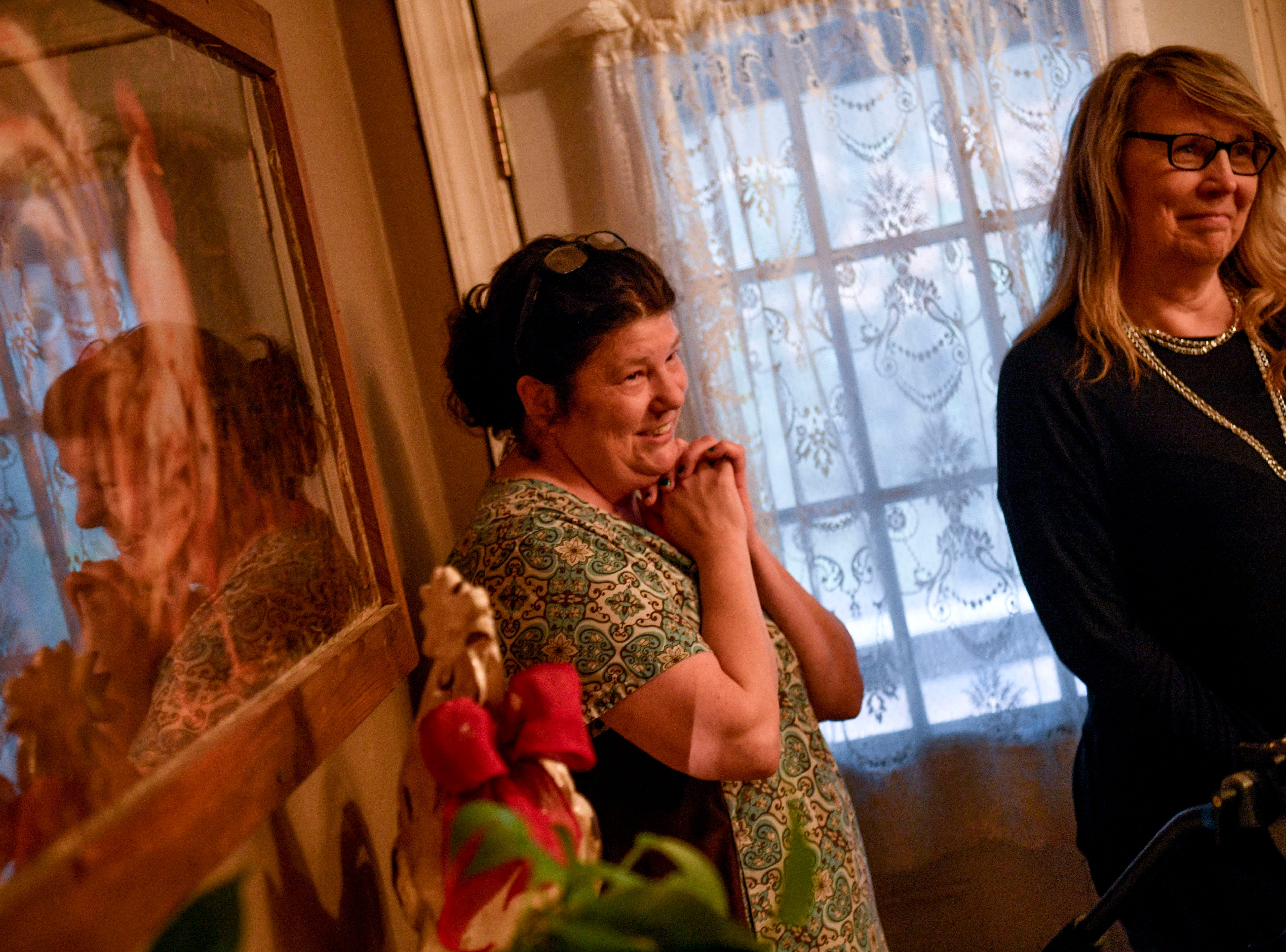 Barbara Elgamal, Zachary Butler's caregiver, and Nancy Hunt, Butler's aunt, smile and watch on as Butler plays poker with Elvis at Butler's home in Trezevant, Tenn., on Wednesday, Jan. 23, 2019.