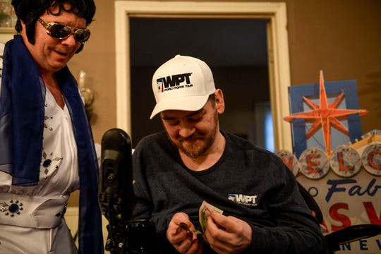 Zachary Butler looks down and counts money that was donated to him and his trip after winning a poker game against Elvis at Butler's home in Trezevant, Tenn., on Wednesday, Jan. 23, 2019.