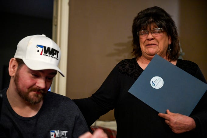 Cindy Mayberry, right, Zachary Butler's mother, becomes emotional and places a hand on her son after he is presented with his trip to Vegas to see his favorite poker player and played a game with Elvis all in the same day at Butler's home in Trezevant, Tenn., on Wednesday, Jan. 23, 2019.