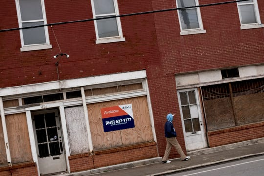 A pedestrian walks in front of a boarded up building on Sevier Avenue and Barber Street in Knoxville, Tennessee on Thursday, January 24, 2019.