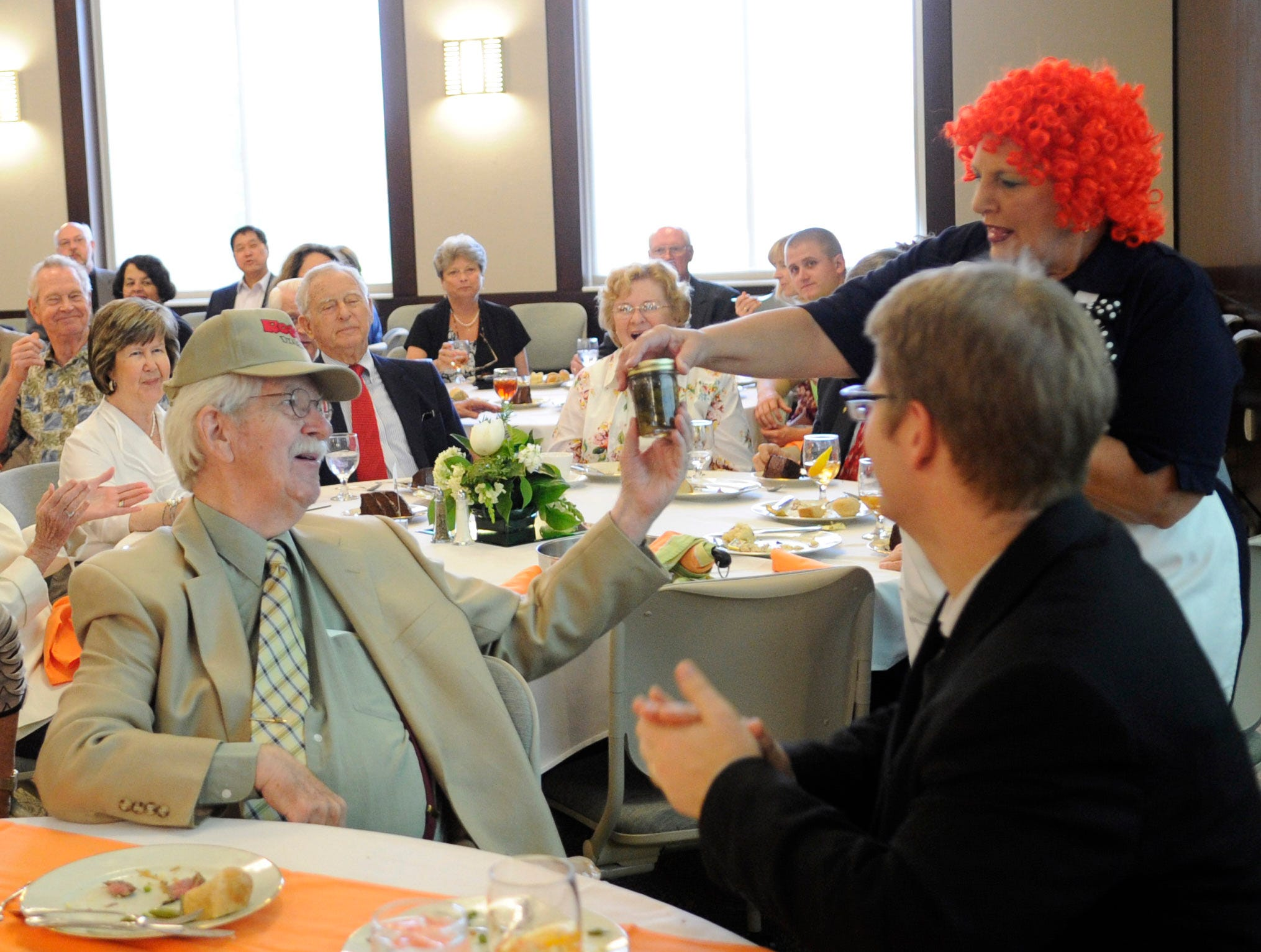 """""""Rosie"""" played by Kathy Burnett, right, presents a jar of sweet pickles to Charlie Daniel, left, as former Senators Howard Baker and Nancy Kassebaum celebrate the work of the Knoxville News Sentinel cartoonist at the Baker Center on Thursday, May 17, 2012. Seated next to Mr. Daniel is his wife Patsy Daniel."""