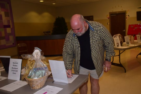 Pastor Larry Dial gets the silent auction started by placing a bid for a $100 gift card from Kirby's Nursery and Landscaping at Beaver Ridge United Methodist Church chili cookoff Saturday, Jan. 19.