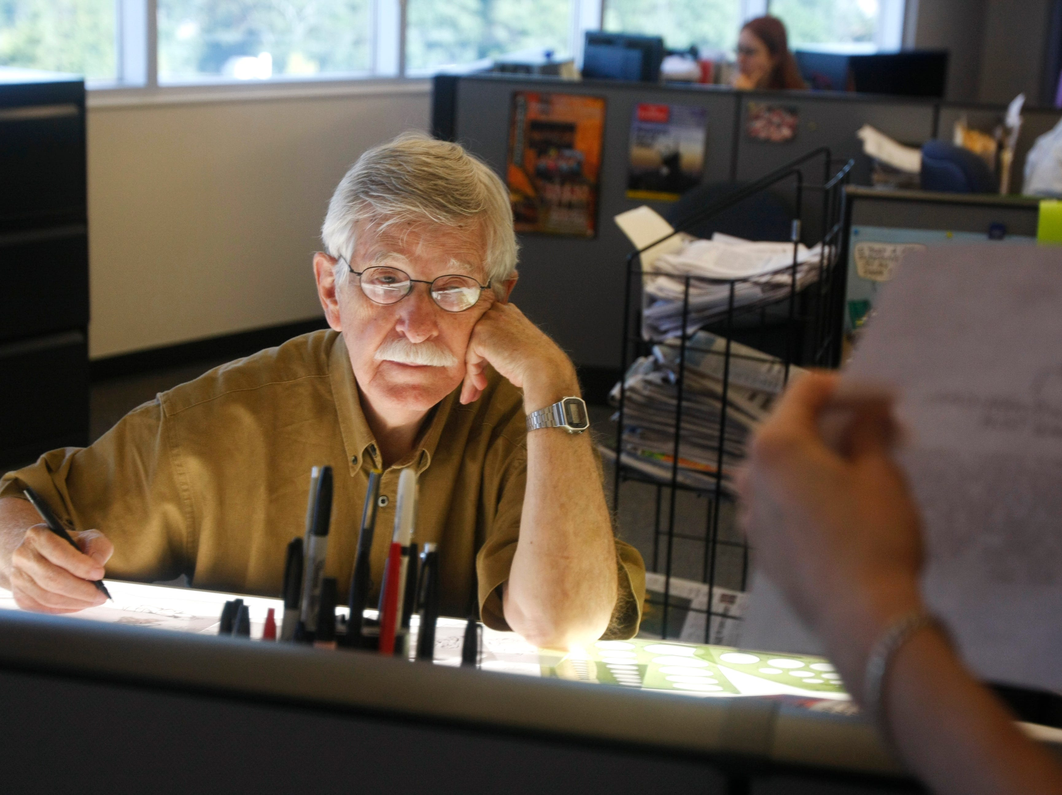 Charlie Daniel, Editorial Cartoonist for the News Sentinel, pauses from drawing to answer a question from a co-worker. Daniel is celebrating 50 years of cartooning in Knoxville staring with his first job at the Knoxville Journal. Tuesday, July 1, 2008