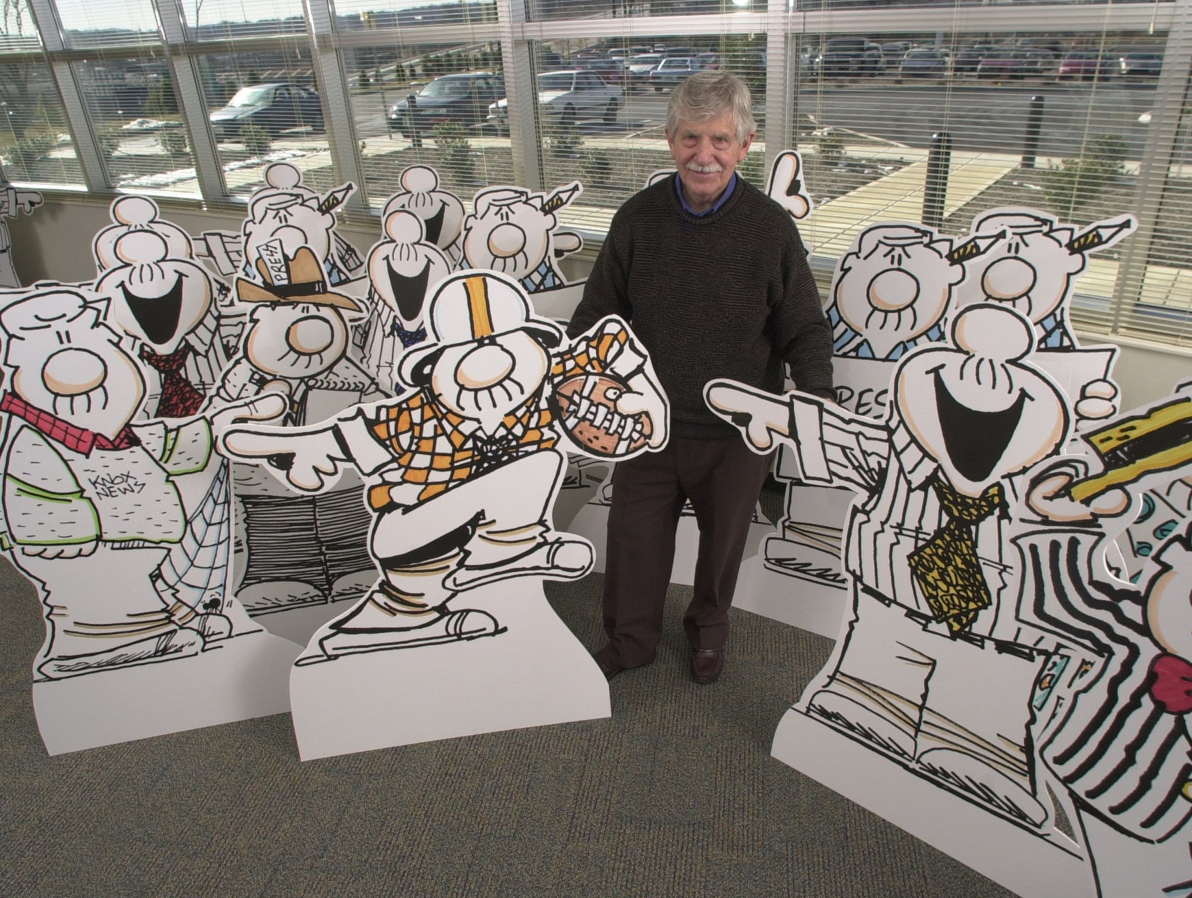 Editorial cartoonist Charlie Daniel pauses with some of the 33 Smidlap stand-ups that will used during an corporate open house Monday at the Knoxville News-Sentinel. 2003.