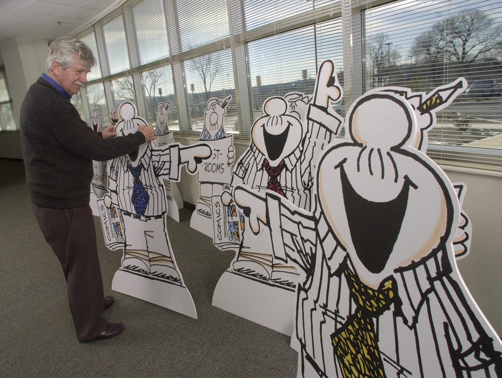 Editorial cartoonist Charlie Daniel checks some of the 33 stand-ups of his alter ego, Smidlap, that will be deployed during an corporate open house Monday at the Knoxville News-Sentinel. Over 100 of Daniel's cartoons and illustrations will be exhibited from Jan. 30 to March 19 at East Tennessee University's Carroll Reece Museum in Johnson City.