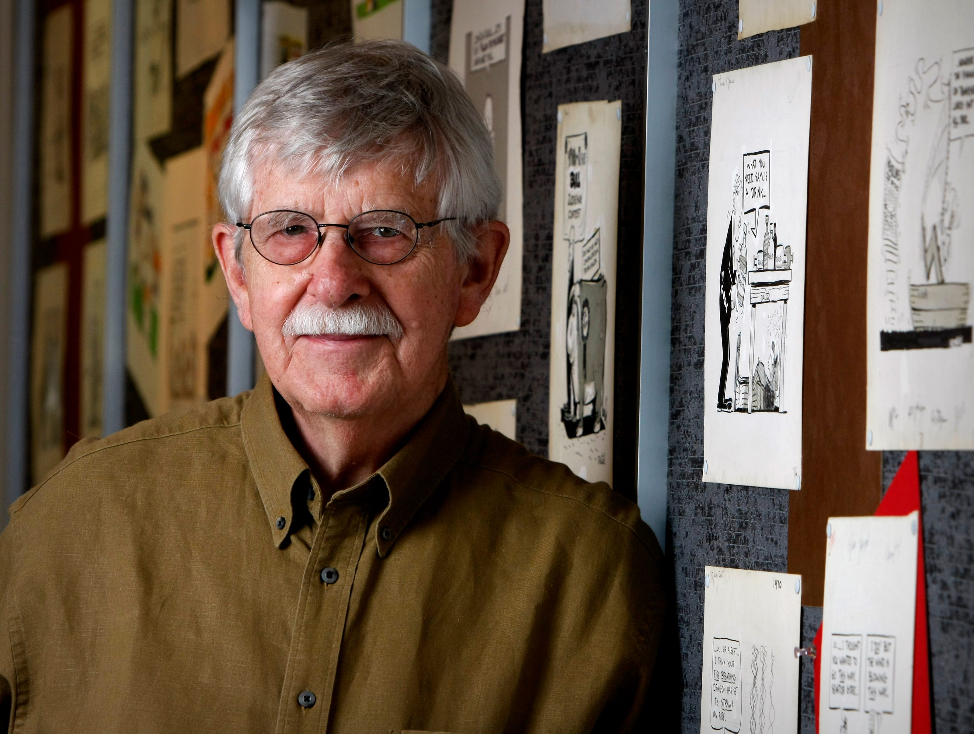 Charlie Daniel, Editorial Cartoonist for the News Sentinel, stands next to his original drawings that are on display at the News Sentinel to honor his 50 year career as a cartoonist in Knoxville. Tuesday, July 1, 2008