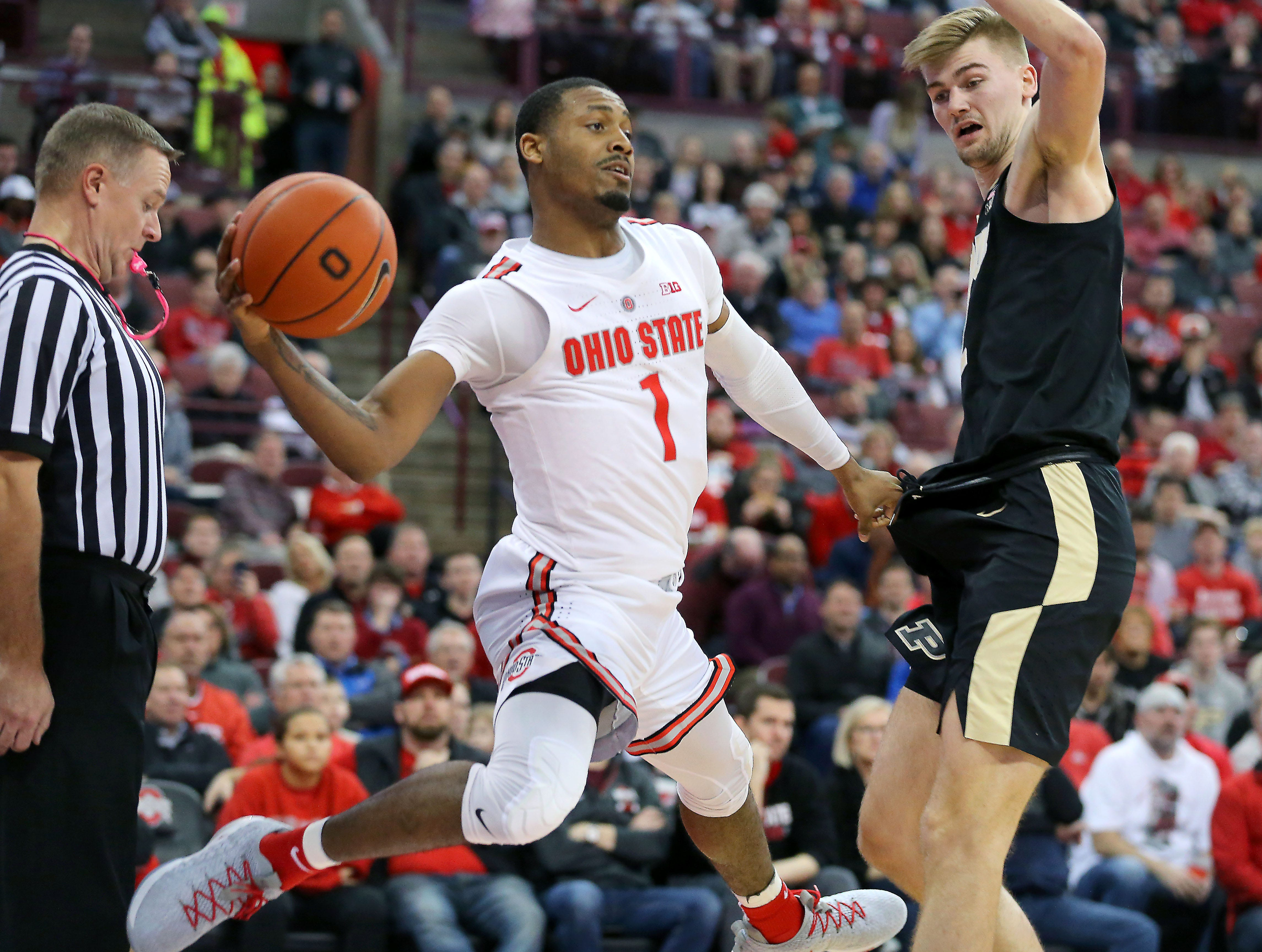 Jan 23, 2019; Columbus, OH, USA; Ohio State Buckeyes guard Luther Muhammad (1) saves the ball as Purdue Boilermakers center Matt Haarms (32) defends during the first half at Value City Arena. Mandatory Credit: Joe Maiorana-USA TODAY Sports