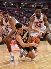 Grady Eifert wrestles for control of a loose ball in the second half with Ohio State's Kaleb Wesson and Andre Wesson on at Value City Arena in Columbus, Ohio.